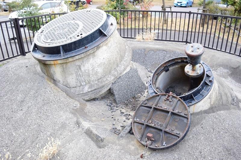 浦安市高洲の「高洲中央公園」の駐車場で、存在感を示す高さ約1メートルのマンホール。液状化被害の象徴として残すことに賛否が巻き起こった